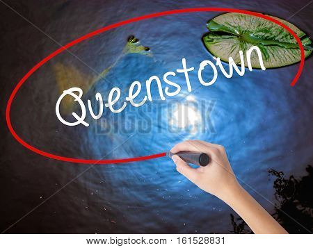 Woman Hand Writing Queenstown  With Marker Over Transparent Board
