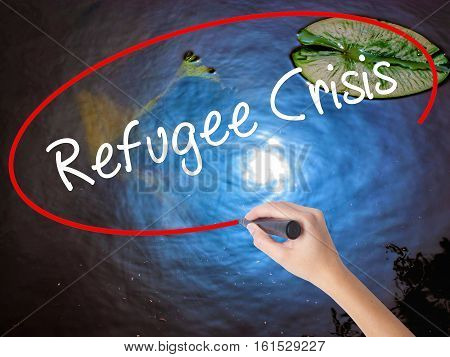 Woman Hand Writing Refugee Crisis With Marker Over Transparent Board