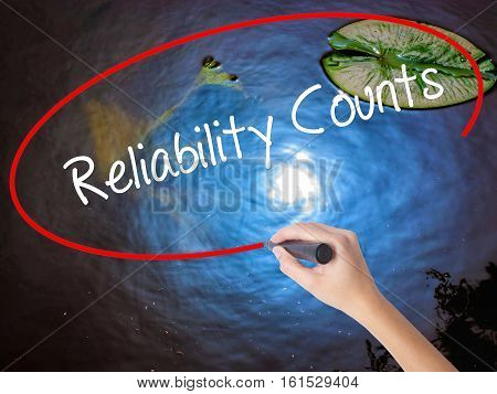 Woman Hand Writing Reliability Counts With Marker Over Transparent Board