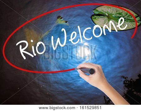 Woman Hand Writing Rio Welcome With Marker Over Transparent Board.