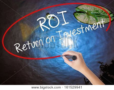 Woman Hand Writing Roi  Return On Investment With Marker Over Transparent Board