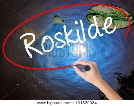 Woman Hand Writing Roskilde With Marker Over Transparent Board