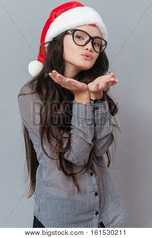 Vertical image of asian woman in christmas hat sands air kiss. Isolated gray background