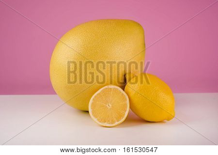 Mixed citrus fruit including lemon and pomelo isolated on a pink background