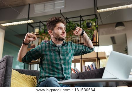 Tired man in green shirt sitting and stretching on sofa by the table with laptop. Image from below. Coworking