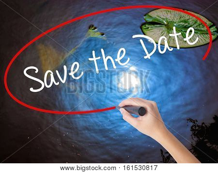 Woman Hand Writing Save The Date  With Marker Over Transparent Board