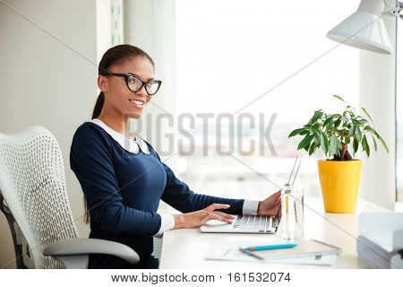 African business woman in dress sitting on armchair in office and looking at camera.