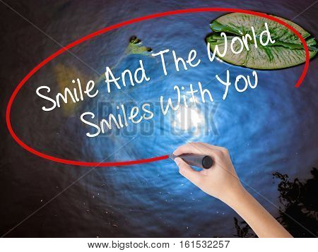 Woman Hand Writing Smile And The World Smiles To You With Marker Over Transparent Board