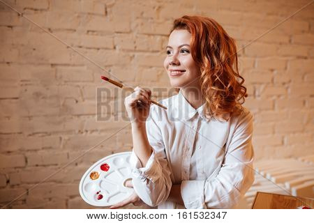 Image of happy young redhead woman painter with oil paints and palette. Look aside.