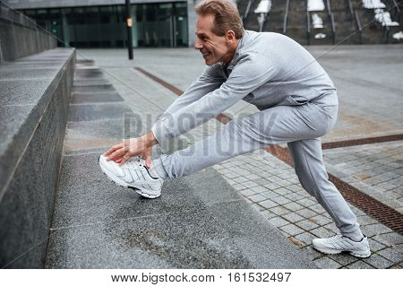 Runner warming up on the street. Full lengt image. Side view