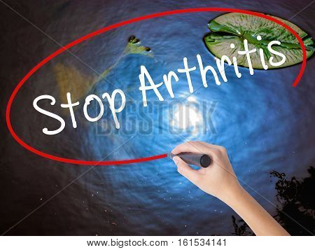 Woman Hand Writing Stop Arthritis With Marker Over Transparent Board