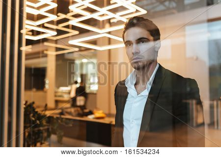 Serious business man in suit behind the glass in office looking aside