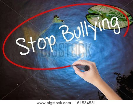 Woman Hand Writing Stop Bullying With Marker Over Transparent Board