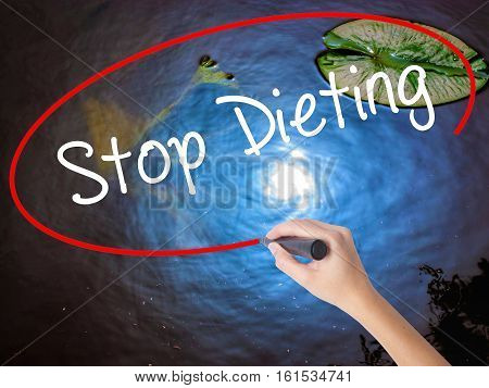 Woman Hand Writing Stop Dieting With Marker Over Transparent Board.