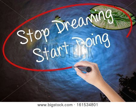 Woman Hand Writing Stop Dreaming Start Doing  With Marker Over Transparent Board