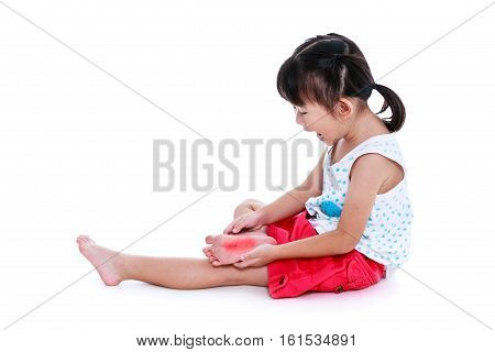 Full body of asian child injured at sole red spot indicating location of pain. Girl screaming. Isolated on white background with copy space. Studio shot. Human health care and problem concept.