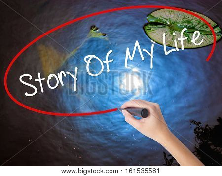 Woman Hand Writing Story Of My Life With Marker Over Transparent Board