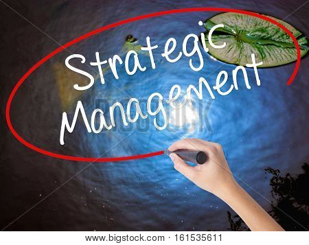 Woman Hand Writing Strategic Management With Marker Over Transparent Board.