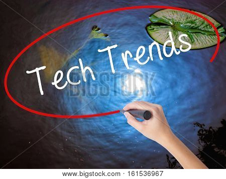 Woman Hand Writing Tech Trends With Marker Over Transparent Board