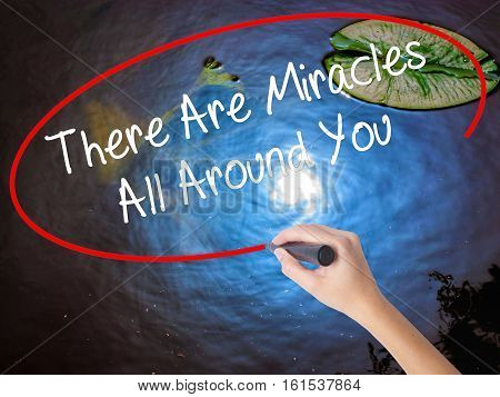 Woman Hand Writing There Are Miracles All Around You  With Marker Over Transparent Board