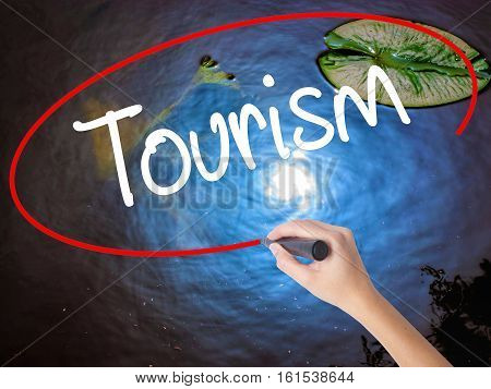 Woman Hand Writing Tourism With Marker Over Transparent Board.