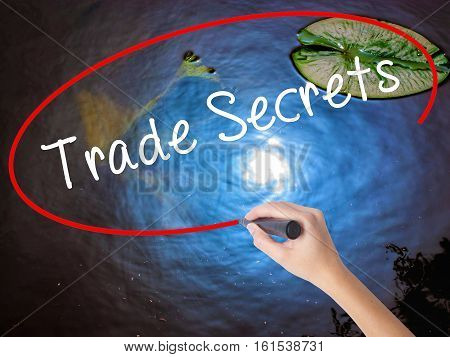 Woman Hand Writing Trade Secrets With Marker Over Transparent Board