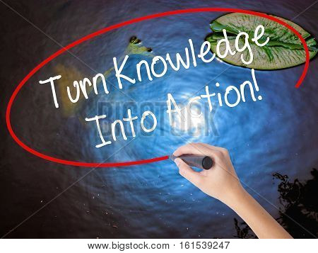 Woman Hand Writing Turn Knowledge Into Action! With Marker Over Transparent Board