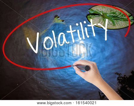 Woman Hand Writing Volatility With Marker Over Transparent Board