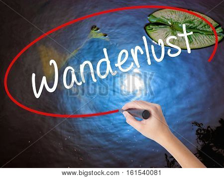 Woman Hand Writing Wanderlust With Marker Over Transparent Board