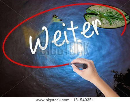 Woman Hand Writing Weiter (continue In German)  With Marker Over Transparent Board