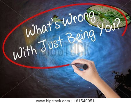 Woman Hand Writing What's Wrong With Just Being You? With Marker Over Transparent Board