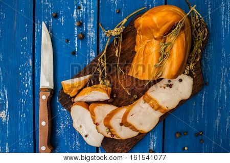 Smoked chicken fillets. Wooden background. Top view