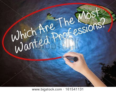 Woman Hand Writing Which Are The Most Wanted Professions? With Marker Over Transparent Board