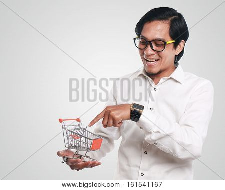 Photo image portrait of a funny young Asian businessman looked happy and smiling while pointing to a small shopping trolley close up portrait consumer concept