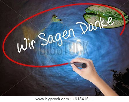 Woman Hand Writing Wir Sagen Danke (we Say Thank You In German)   With Marker Over Transparent Board