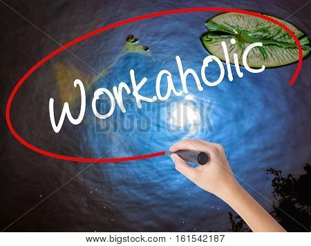 Woman Hand Writing Workaholic With Marker Over Transparent Board