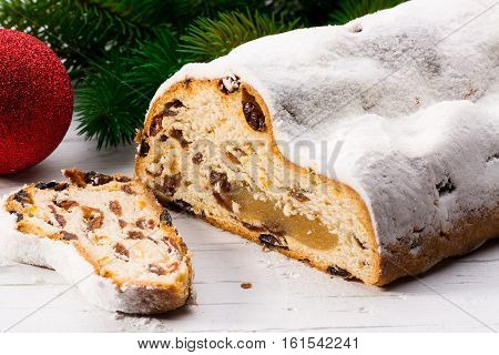 Christmas stollen with green branch and red christmas ball on white wooden board.