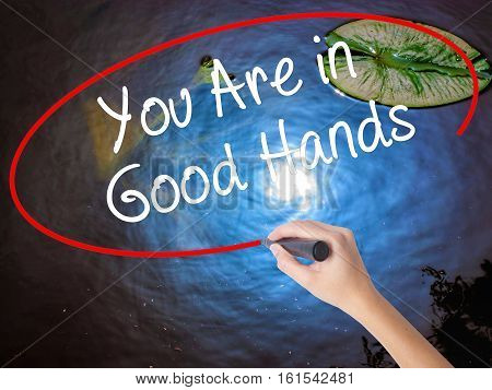 Woman Hand Writing You Are In Good Hands With Marker Over Transparent Board