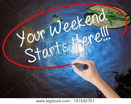 Woman Hand Writing Your Weekend Starts Here!!! With Marker Over Transparent Board