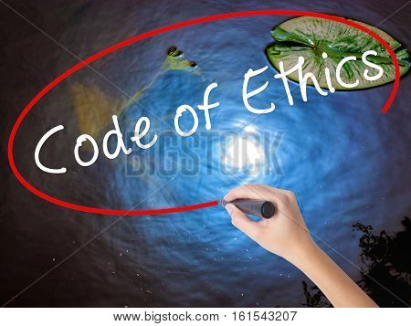 Woman Hand Writing Code Of Ethics With Marker Over Transparent Board