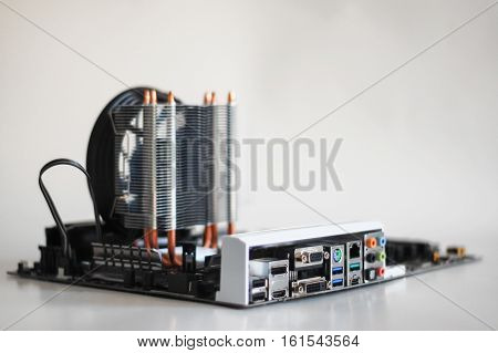 PC Computer mother or main board with heat sink cooler for processor, on white background. DVI, VGA, HDMI, Display Port, USB, PS, Audio connections on back panel.