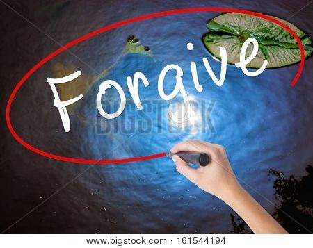 Woman Hand Writing Forgive With Marker Over Transparent Board