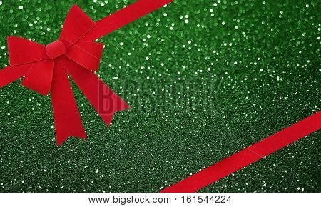 Large red Christmas bow isolate on green glitter bokeh background
