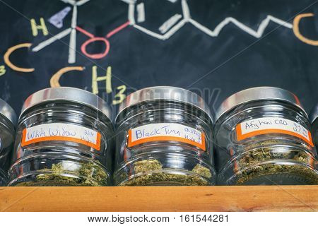 Medical marijuana jars against board with THC formula - cannabis dispensary background