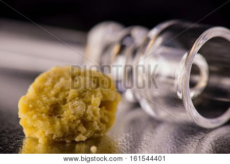 Marijuana extraction concentrate aka wax crumble on dark background with glass rig