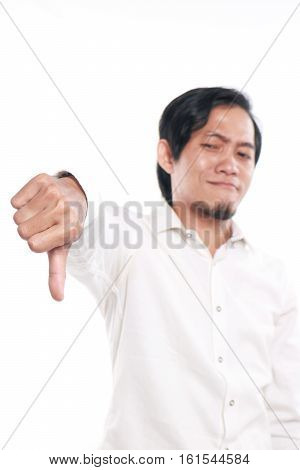 Photo image portrait of a cute funny young Asian man showing thumb down gesture with mocking face close up portrait over white background