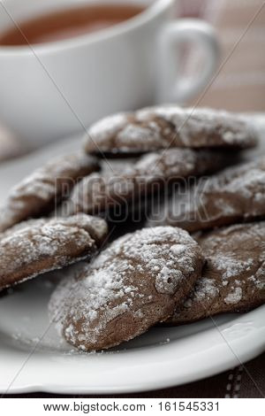 Gooey Butter Cookies on a plate against a cup of tea. Selected focus on the front cookies