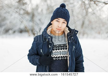 Man In Knitted Hat And Knitted Sweater With A Pattern And A Jacket On A Background Of A Winter Park