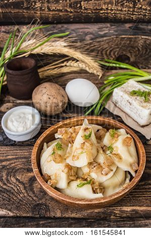 Boiled dumplings with potatoes. Wooden background, ravioli