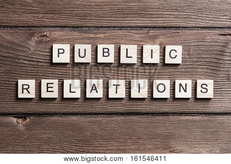 Wooden elements element on wooden table spelling words public relations